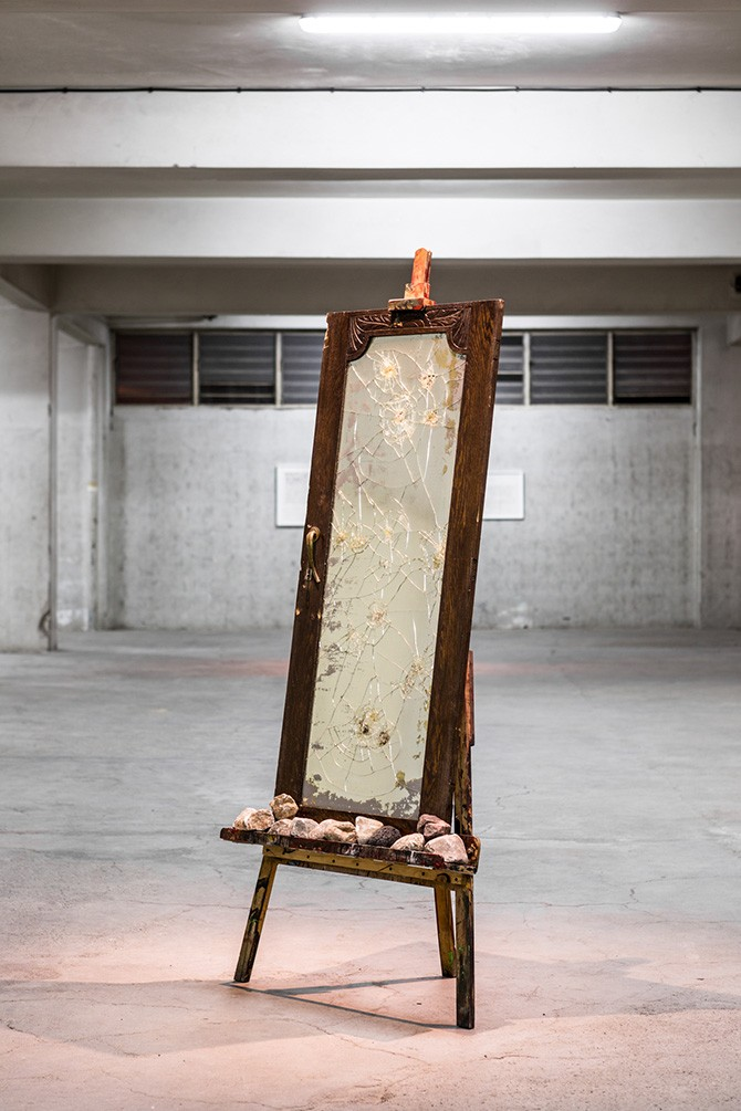 Dimitris Merantzas, Self portrait by stoning, 2012. Wooden easel, closet door with broken mirror and key, 12 stones, 206 × 80 × 60 cm. Photography: Antonis Minas, Courtesy the Office gallery. All rights reserved.