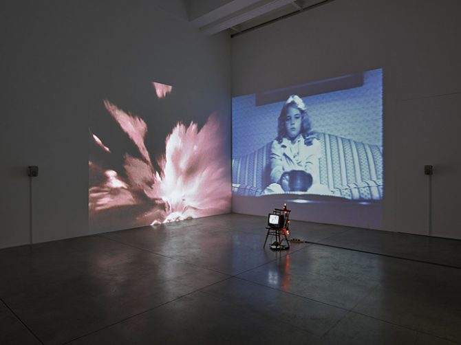 Susan Hiller, Wild Talents, 1997. Video installation: two channel video projection, with sound, one black-and-white video, monitor, chair, and votive lights. Dimensions variable. © Susan Hiller. Courtesy Lisson Gallery. All rights reserved.